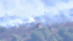 عناصر حزب اللخ تقوم بإشعال الحرائق بالقرب من الحدود الإسرائيلية اللبنانية يوم الجمعة، 16 أغسطس، 2019. (Screencapture/Channel 12)