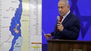 رئيس الوزراء بنيامين نتنياهو يقف أمام خريطة لغور الأردن خلال إلقاء خطاب في رمان غان، 10 سبتمبر، 2019. (Menahem Kahana/AFP)