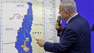 رئيس الوزراء بنيامين نتنياهو يشير الى خريطة لغور الأردن خلال إدلائه بتصريح تعهد فيه ببسط السيادة الإسرائيلية على فور الأردن وشمال البحر الميت، في مدينة رمات غان، 10 سبتمبر، 2019. (Menahem Kahana/AFP)
