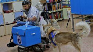 رجل إسرائيلي مقعد برفقة كلبه وببغاء يدلي بصوته في الإنتخابات للكنيست، في مركز اقتراع بتل أبيب، 17 سبتمبر، 2019.  (Gil Cohen-Magen/AFP)