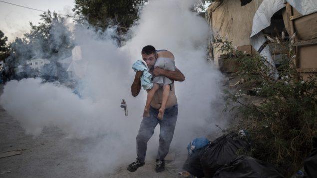 رجل يحمل طفلة خلال اشتباكات مع الشرطة في مخيم موريا للاجئين في جزيرة ليسبوس اليونانية، 20 سبتمبر 2019 (ANGELOS TZORTZINIS / AFP)