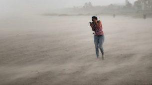 سيدة تحاول الاختباء من الرياح والامطار خلال اعصار دوريان في فلوريدا، 2 سبتمبر 2019 (Scott Olson/Getty Images/AFP)