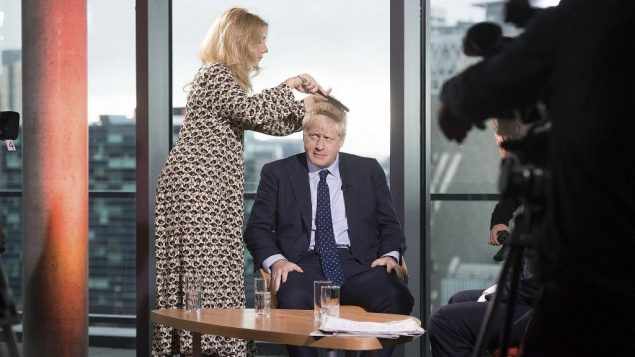 سيدة تمشط شعر رئيس الوزراء البريطاني بوريس جونسون قبل ظهوره في برنامج تلفزيوني سياسي، قبل افتتاح مؤتمر الحزب المحافظ السنوي، 29 سبتمبر 2019 (Stefan Rousseau/PA via AP)
