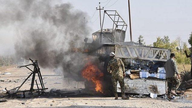 توضيحية: عناصر في قوات الحشد الشعبي تقف بالقرب من شاحنة مشتعلة بعد هجوم لطائرة مسيرة حُمّلت إسرائيل مسؤوليته، بالقرب من معبر القائم الحدودي، في محافظة الأنبار، العراق، 25 أغسطس، 2019. (AP Photo)