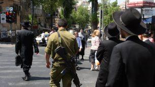 صورة توضيحية: رجال يهود متشددون في حي مئا شعاريم يمشون الى جانب جندي اسرائيلي، 6 يونيو 2008 (Lara Savage/ Flash 90)