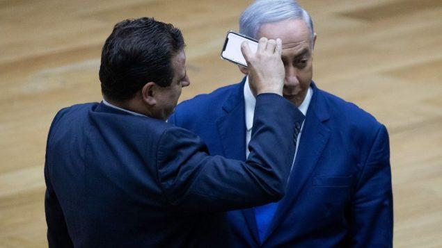قائد القائمة المشتركة ايمن عودة يصور رئيس الوزراء بنيامين نتيناهو خلال مباحثات حول قاتنون الكاميرات في الكنيست، 11 سبتمبر 2019 (Yonatan Sindel/Flash90)