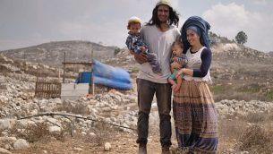 نيريا زاروغ (وسط الصورة) وزوجته وطفليه أمام منزلهم في بؤرة كيبا سروغا الاستيطانية، وهي حي في مستوطنة يتسهار بشمال الضفة الغربية. (Avraham Shapira)