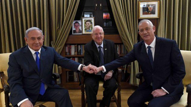 رئيس الوزراء بنيامين نتنياهو يصافح زعيم حزب 'ازرق ابيض' بيني غانتس، والرئيس رؤوفن ريفلين، في مقر اقامة الرئيس في القدس، 23 سبتمبر 2019 (Haim Zach/GPO)