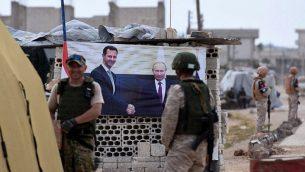 عناصر من الجيش الروسي يقفون بالقرب من لافتة تظهر الرئيس الروسي فلاديمير بوتين، يمينًا، يصافح الرئيس السوري بشار الأسد، عند نقطة تفتيش أبو الزهور في الريف الغربي من محافظة إدلب، 1 يونيو 2019 (George Ourfalian/AFP)