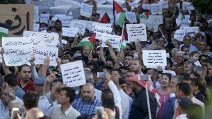 فلسطينيون يشاركون في تظاهرة للمطالبة برفع العقوبات عن قطاع غزة، في مدينة رام الله بالضفة الغربية، 23 يونيو، 2018.  (AFP/ ABBAS MOMANI)