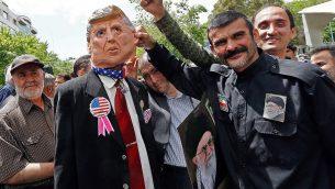 متظاهرون إيرانيون يحملون صورة للمرشد الأعلى الإيراني، آية الله علي خامنئي، وقناع للرئيس الأمريكي دونالد ترامب، خلال مظاهرة في العاصمة طهران، 10 مايو، 2019.  (Stringer/AFP)