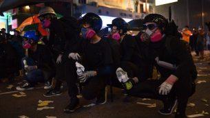 متظاهرون خلال مواجهات مع الشرطة في منطقة 'كوزواي باي' في هونغ كونغ، 1 أكتوبر، 2019، بالتزامن مع احتفالات المدينة ب'اليوم الوطني' لإحياء الذكرى ال70 لتأسيس الصين الشيوعية.   (Photo by Nicolas ASFOURI / AFP)
