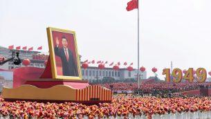 طوافة استعراض تحمل صورة ضخمة للرئيس الصيني شي جين بينغ تمر من ساحة تيانانمين خلال احتفالات 'اليوم الوطني' في بكين، 1 أكتوبر، 2019، لإحياء الذكرى ال70 لتأسيس جمهورية الصين الشعبية. (Photo by GREG BAKER / AFP)