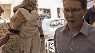 سائحة بريطانية (يسار)، المتهمة بتقديم بلاغ كذب بتعرضها للاغتصاب من قبل سياح إسرائيليين، تغطي وجهها عند وصولها إلى محاكمتها في محكمة مقاعطة فاماغوتسا في بارليمني بشرقي قبرص، 2 أكتوبر، 2019.  (Iakovos HATZISTAVROU/AFP)