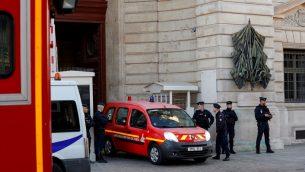 عناصر الشرطة تقف خارج مقر شرطة باريس مع خروج مركبة إطفاء من المقر في 3 أكتوبر، 2019 بعد مقتل أربعة شرطيين في هجوم طعن.  (Photo by GEOFFROY VAN DER HASSELT / AFP)