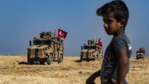 طفل سوري يراقب مركبات عسكرية تركية تشارك في دورية في قرية الحشيشة السورية على أطراف مدينة تل أبيض عند الحدود مع تركيا، ضمن قافلة عسكرية أمريكية، في 4 أكتوبر، 2019. (Delil SOULEIMAN / AFP)