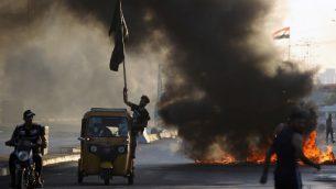 متظاهرون عراقيون يحرقون اارات خلال مظاهرة ضد الفساد الحكومي، تراجع الخدمات العامة، والبطالة، في العاصمة العراقية بغداد، 5 اكتوبر 2019 (AHMAD AL-RUBAYE / AFP)