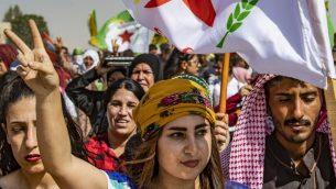 أكراد سوريون يتظاهرون ضد التهديدات التركية ضد التهديدات التركية بالقرب من قاعدة للتحالف الدولي بقيادة الولايات المتحدة على أطراف بلدة راس العين في محافظة الحسكة السورية بالقرب من الحدود مع تركيا، 6 أكتوبر، 2019.  (Delil SOULEIMAN / AFP)