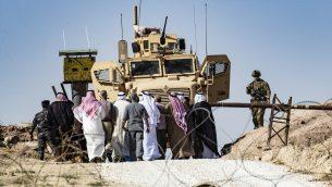 اكراد سوريون يتظاهرون ضد التهديدات التركية، بالقرب من قاعدة تابعة للتحالف الدولي الذي توقده الولايات المتحدة، في ضواحي بلدة راس العين في محافظة الحسكة السورية، بالقرب من الحدود التركية، 6 اكتوبر 2019 (Delil Souleiman/AFP)
