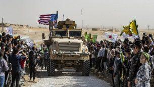 اكراد سوريون يتظاهرون حول مركبة مدرعة امريكية ضد التهديدات التركية، بالقرب من قاعدة تابعة للتحالف الدولي الذي توقده الولايات المتحدة، في ضواحي بلدة راس العين في محافظة الحسكة السورية، بالقرب من الحدود التركية، 6 اكتوبر 2019 (Delil Souleiman/AFP)