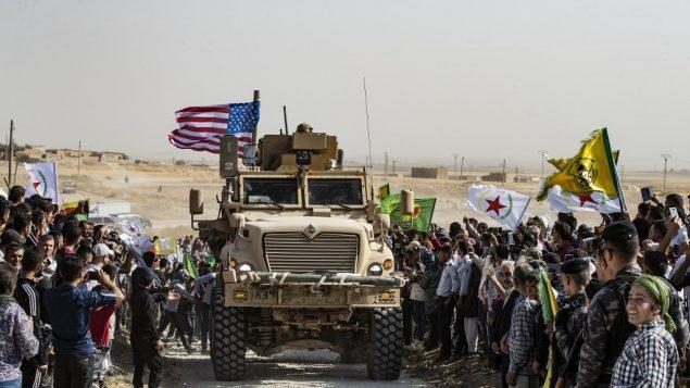 أكراد سوريون يحتشدون حول مدرعة أمريكية خلال تظاهرة ضد التهديدات التركية بالقرب من قاعدة للتحالف الدولي بقيادة الولايات المتحدة على أطراف بلدة راس العين في محافظة الحسكة السورية بالقرب من الحدود مع تركيا، 6 أكتوبر، 2019.  (Delil SOULEIMAN / AFP)