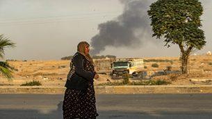 امرأة سورية تمشي امام دخان بينما يفر مدنيون عرب وأكراد بعد القصف التركي على بلدة رأس العين بشمال شرق سوريا في محافظة الحسكة على الحدود التركية، 9 اكتوبر 2019 (DELIL SOULEIMAN / AFP)