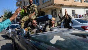 مقاتلون معارضون سوريون مدعومون من تركيا يتوجهون إلى تل الأبيض من البوابة التركية باتجاه سوريا في أكاكالي، 10 أكتوبر 2019. (BULENT KILIC/AFP)