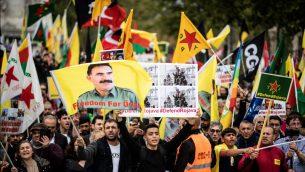 أشخاص يرفعون أعلاما ولافتات مناصرة للأكراد في باريس، 12 أكتوبر، 2019، خلال تظاهرة مؤيدة للمقاتلين الأكراد واحتجاج على استمرار التدخل العسكري التركي على البلدات الحدودية التي يسيطر عليها الأكراد في شمال شرق سوريا، في اليوم الرابع من الهجوم الذي أثار إدانات دولية، حتى من واشنطن.   (Martin BUREAU / AFP)