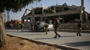 مقاتلون سوريون موالون لتركيا يسيرون في أحد شوارع مدينة تل أبيض السورية في 13 أكتوبر، 2019، في اليوم الخماس من الهجوم التركي في سوريا. ( Bakr ALKASEM / AFP)
