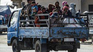 عائلات سورية تفر من منطقة المعارك بين قوات تقودها تركيا ومقاتلين أكراد من قوات سوريا الديمقراطية داخل مدينة الرأس الأبيض وفي محيطها على الحدود مع تركيا، 15 أكتوبر، 2019.  (Delil SOULEIMAN/AFP)