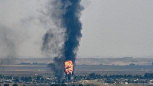 صورة التقطت من الجانب التركي من الحدود بين تركيا وسوريا، في سيلانبار بمقاطعة سانليورفا، تظهر دخان ونيران تتصاعد من بلدة رأس العين السورية، خلال الهجوم التركي ضد فصائل كردية في شمال شرق سوريا، 17 اكتوبر 2019 (Ozan Kose/AFP)