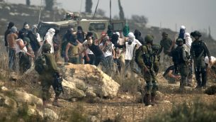 صورة توضيحية: جنود إسرائيليون يقفون امام مستوطنين إسرائيليين ملثمين يقومون بإلقاء الحجارة على متظاهرين فلسطينيين، خلال مظاهرة ضد البناء في بؤرة استياطنية إسرائيلية بالقرب من قرية ترمسعيّا الفلسطينية ومستوطنة شيلو، شمال رام الله في الضفة الغربية ، 17 أكتوبر 2019 (JAAFAR ASHTIYEH / AFP)
