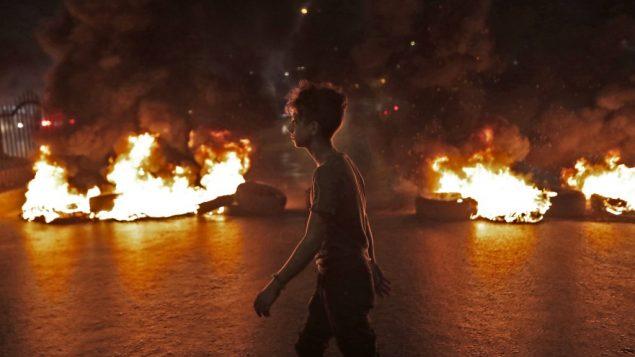 متظاهر لبناني يمشي امام إطارات محترقة أثناء احتجاج على قرارات ضريبية أخيرة، في صاحية بيروت الجنوبية، 17 اكتوبر 2019 (ANWAR AMRO / AFP)