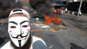 """متظاهر يضع قناع غاي فوكس خلال احتجاجات ضد الأوضاع الاقتصادية الصعبة في حي """"سليم سلام"""" ببيرت، 18 أكتوبر، 2019.  ( IBRAHIM AMRO / AFP)"""