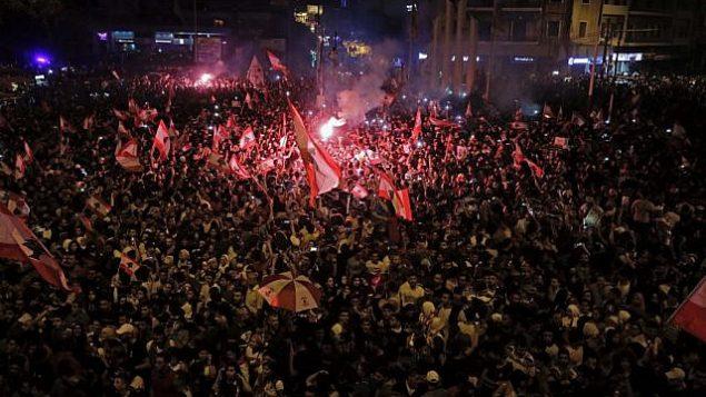 متظاهرون لبنانيون يلوحون بالأعلام الوطنية أثناء مشاركتهم في مظاهرة في مدينة طرابلس الشمالية خلال اليوم الرابع من المظاهرات ضد زيادة الضرائب والفساد الحكومي، 20 أكتوبر 2019. (Ibrahim Chalhoub/AFP)