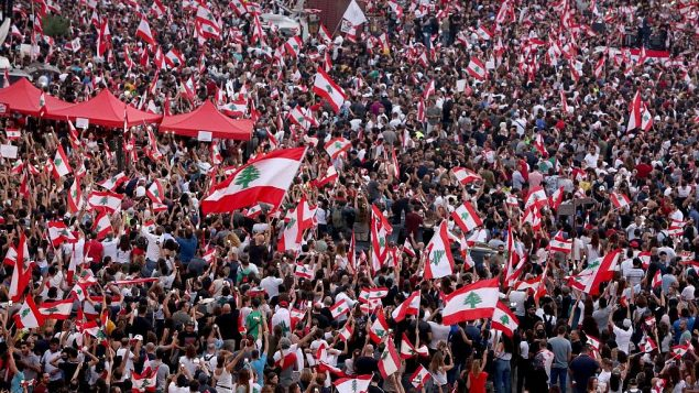 متظاهرون لبنانيون يلوحون بالأعلام الوطنية أثناء مشاركتهم في مظاهرة في وسط العاصمة بيروت, 20 أكتوبر 2019. (Patrick Baz/AFP)