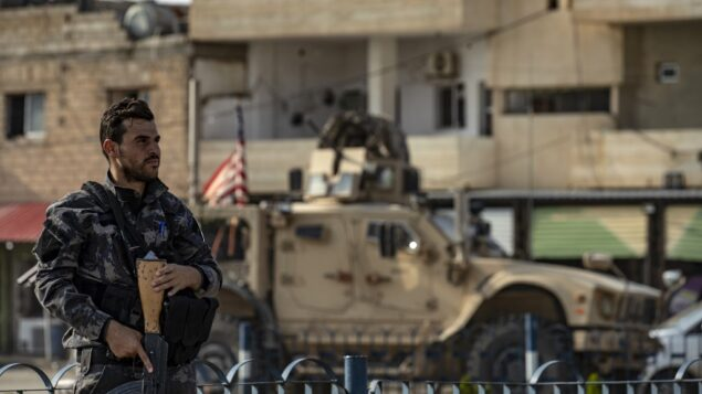 مقاتل من قوات سوريا الديمقراطية يحرس بينما مركبة عسكرية أمريكية تنسحب من قاعدة للقوات الأمريكية في بلدة تل تمر، شمال سوريا، 20 أكتوبر 2019. (Delil SOULEIMAN / AFP)