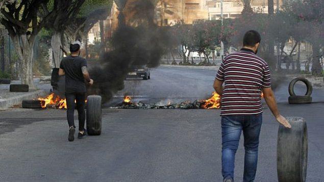 متظاهرون لبنانيون مناهضون للحكومة يسدون طريقاً بإطارات محترقة في مدينة صيدا الساحلية الجنوبية، 21 أكتوبر 2019 (Mahmoud ZAYYAT / AFP)
