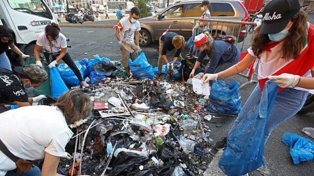 متظاهرون لبنانيون ينظفون القمامة من شوارع وسط العاصمة بيروت بعد ليلة من الاحتجاجات على زيادة الضرائب والفساد الحكومي، 21 أكتوبر 2019 (ANWAR AMRO / AFP)