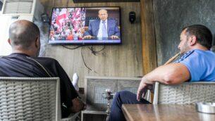 رجال لبنانيون يدخنون النرجيلة وهم يشاهدون خطابًا متلفزًا للرئيس ميشال عون، في مقهى في العاصمة بيروت في 24 أكتوبر 2019، بينما يخاطب عون المتظاهرين في اليوم الثامن من الاحتجاجات على زيادة الضرائب والفساد الحكومي (IBRAHIM AMRO / AFP)