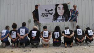 نشطاء إسرائيليون يتظاهرون تضامنا مع المواطنة الأردنية هبة اللبدي (الظاهرة في الصورة)، المحتجزة حاليا في السجون الإسرائيلية ومضربة عن الطعام، من أمام سجن عوفر خلال جلسة للبت في قضيتها في الضفة الغربية، 28 أكتوبر، 2019.  (AHMAD GHARABLI / AFP)