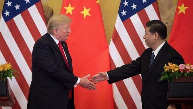 الرئيس الأمريكي دونالد ترامب (يسار) يصافح الرئيس الصيني شي جين بينغ في نهاية مؤتمر صحفي في قاعة الشعب الكبرى في بكين، 9 نوفمبر 2017. (AFP/Nicolas Asfouri)