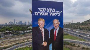 عامل يقوم بتعليق  لوحة إعلانية ضخمة تحمل صورة الرئيس الأمريكي دونالد ترامب ورئيس الوزراء الإسرائيلي بنيامين نتنياهو، في إطار الحملة الإنتخابية لحزب 'الليكود' في تل أبيب، 19 سبتمبر، 2019. على اللوحة كُتب 'نتنياهو،  في مستوى آخر'. (AP/Oded Balilty)
