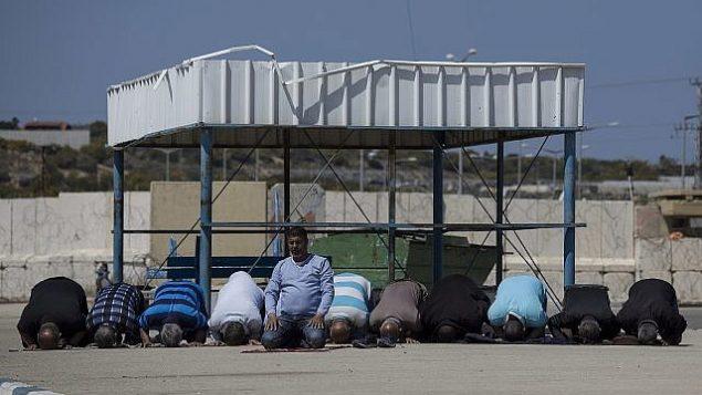 """في هذه الصورة من 26 مارس، 2017، سكان فلسطينيون من قطاع غزة يؤدون الصلاة خلال انتظارهم على الجانب الإسرائيلي من معبر """"إيرز"""" لدخول غزة.  (AP Photo/Tsafrir Abayov, File)"""