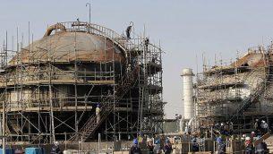خلال جولة نظمتها وزارة الاتصالات السعودية، عمال يصلحون الأضرار التي لحقت بمنشأة تكرار نفط تابعة لشركة 'آرامكو' بعد الهجوم الذي وقع في 14 سبتمبر في بقيق، بالقرب من الدمام في  في المنطقة الشرقية للمملكة ، 20 سبتمبر 2019. (AP Photo / Amr Nabil)