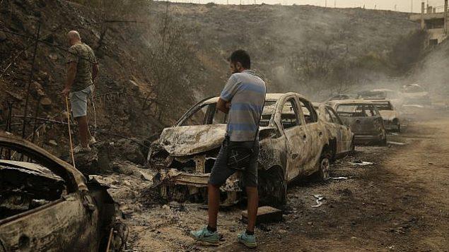 أشخاص يتفقدون حطام مركبات ومحلات تجارية أتت عليها النيران جراء حرائق اندلعت فجرا في بلدة دامور التي تبعد 15 كيلومترا جنوب بيروت، لبنان، 15 أكتوبر، 2019.  (AP Photo/Hassan Ammar)