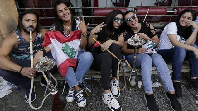 محتجون مناهضون للحكومة يدخنون ارجيلة خلال مظاهرة في بيروت، لبنان، 20 أكتوبر 2019. (AP Photo / Hassan Ammar)