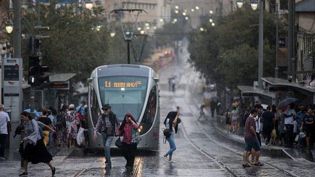 أشخاص يسيرون في أحوال جوية ماطرة وعاصفة في شارع يافا بالقدس، 15 أكتوبر، 2019. (Yonatan Sindel/Flash90)