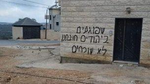عبارة 'عندما يتعرض اليهود للإذى، من واجبنا ألا ننسى' تم خطها على جدار في قرية قيرة الفلسطينية في ما يُشتبه بأنها جريمة 'تدفيع ثمن'، 6 أكتوبر، 2019.  (Ouhoud Khafash/Yesh/Din)