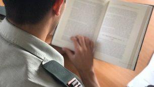 صورة توضيحية صدرت في 16 اكتوبر 2019، تظهر ضابط عسكري اسرائيلي يقرأ كتاب (Israel Defense Forces)